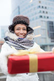 Happy woman holding gift during winter in city Royalty Free Stock Photography
