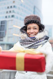 Happy woman holding gift during winter in city Stock Images