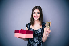 Happy woman holding glass of champagne and gift box Stock Images