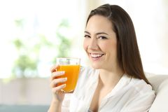 Woman holding a glass of orange juice at home. Happy woman holding a glass of orange juice sitting on a couch in the living room at home Stock Image