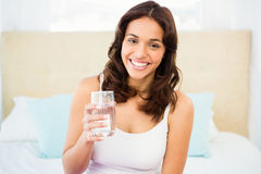 Happy woman holding glass of water while sitting on bed Stock Photos
