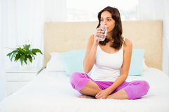 Happy woman holding glass of water while sitting on bed royalty free stock photos