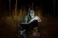 Happy woman holding glowing book at night forest Stock Photo