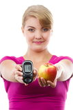 Happy woman holding glucometer and fresh apple, measuring sugar level, concept of diabetes Royalty Free Stock Photos