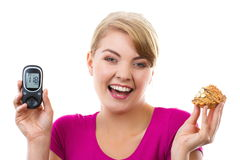 Happy woman holding glucometer and fresh cupcake, measuring and checking sugar level, concept of diabetes Royalty Free Stock Photos