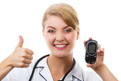 Happy woman holding glucometer and showing thumbs up, checking and measuring sugar level, concept of diabetes Stock Photo