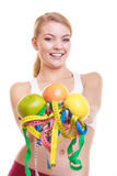 Happy woman holding grapefruits and tape measures. Stock Photos