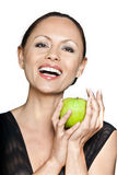 Happy woman holding green apple. Closeup portrait of happy beautiful Asian woman holding green apple in studio isolated on white background Royalty Free Stock Photography