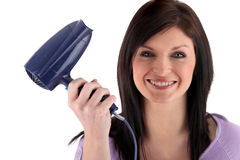 Happy woman holding hairdryer Stock Photo