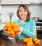 Happy  woman holding  heap of mandarins Stock Images