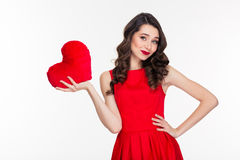 Happy woman holding heart. Portrait of a happy woman in red dress holding heart isolated on a white background Royalty Free Stock Photo