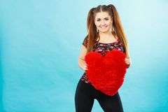 Happy woman holding heart shaped pillow Stock Image
