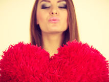 Happy woman holding heart shaped pillow. Love, valentines day gift idea concept. Happy woman with brown hair holding heart shaped pillow sending air kiss Stock Photography
