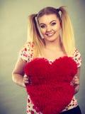 Happy woman holding heart shaped pillow Stock Photo