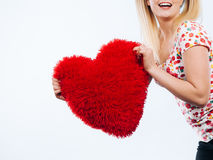 Happy woman holding heart shaped pillow Royalty Free Stock Photos