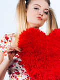 Happy woman holding heart shaped pillow Royalty Free Stock Photography