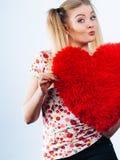 Happy woman holding heart shaped pillow Stock Photos