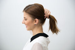 Happy woman holding her hair. Side view portrait of a happy woman holding her hair Stock Images