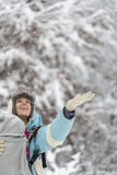 Happy woman holding her hand out to winter snow. Warmly dressed happy woman holding her hand out to the winter snow during a fresh snowfall as she enjoys a walk Royalty Free Stock Images