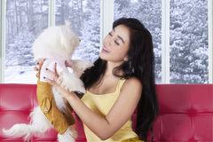 Happy woman holding her puppy at home Stock Photo
