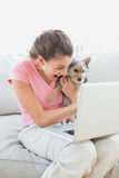Happy woman holding her yorkshire terrier on the couch using laptop Stock Photography