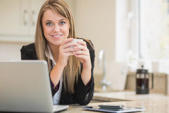 Happy woman holding hot beverage with laptop Stock Photos