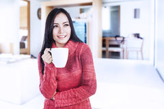 Happy woman holding hot coffee at home. Beautiful happy smiling woman dressed with winter clothes holding a hot cup of coffee at home Stock Photos