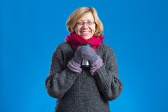 Happy woman holding hot thermal mug. Happy woman wearing gloves and scarf holding hot thermal mug Stock Photo