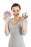 Happy woman holding house model and euro bills Royalty Free Stock Images