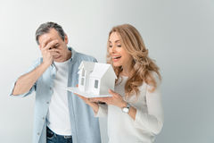 Happy woman holding house model with husband near by on grey royalty free stock photo