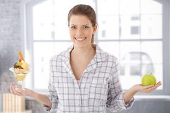 Happy woman holding icecream cup and apple Stock Images