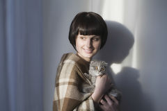 Happy Woman Holding Kitten Against Wall Stock Images