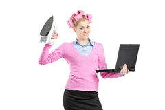 Happy woman holding a laptop and an iron Stock Images