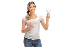 Happy woman holding a LED light bulb and pointing Royalty Free Stock Photos