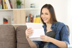 Happy woman holding a letter at home. Happy woman holding a letter sitting on a couch in the living room at home Stock Photo
