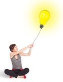 Happy woman holding a light bulb balloon Royalty Free Stock Photo