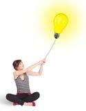 Happy woman holding a light bulb balloon. Happy young woman holding a light bulb balloon Royalty Free Stock Photo