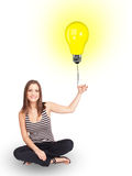 Happy woman holding a light bulb balloon. Happy young woman holding a light bulb balloon Royalty Free Stock Images