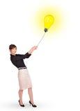 Happy woman holding a light bulb balloon Stock Photo
