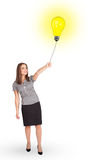 Happy woman holding a light bulb balloon Stock Photos