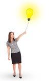 Happy woman holding a light bulb balloon Stock Photos