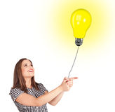 Happy woman holding a light bulb balloon Stock Photo