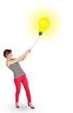 Happy woman holding a light bulb balloon Stock Photography