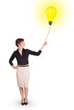 Happy woman holding a light bulb balloon. Happy young woman holding a light bulb balloon Stock Images
