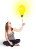 Happy woman holding a light bulb balloon Stock Image