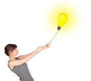 Happy woman holding a light bulb balloon Stock Photography