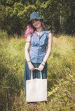Happy woman holding linen bag in summer field. Template mock up Stock Photography