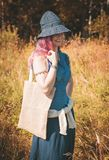 Happy woman holding linen bag in summer field. Template mock up Stock Images