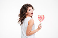 Happy woman holding lollipop and looking back at camera Stock Image