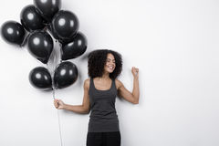 Happy woman holding many black balloons Stock Images